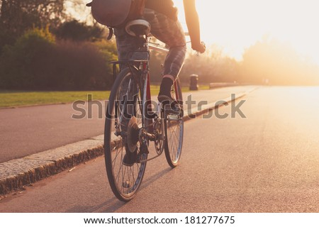 A young woman is cycling into the sunset in the park Royalty-Free Stock Photo #181277675