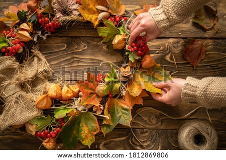 Making wreath autumn colorful leaves and natural materials on rustic wooden boards. Top view women's hands make round wreath autumn harvest and foliage on brown wooden table. Decoration for interior. #1812869806