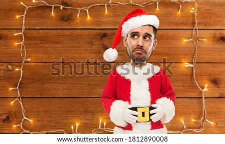 emotion, facial expressions and people concept - sad young man in costume of santa over garland lights on wooden background (funny cartoon style character with big head)