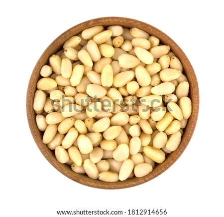 Bowl with pine nuts on white background, delicious, natural Royalty-Free Stock Photo #1812914656