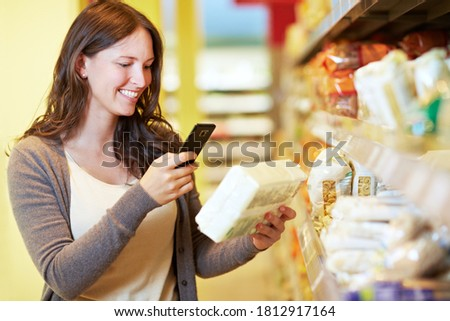 Smiling woman scans the barcode of a product in the supermarket