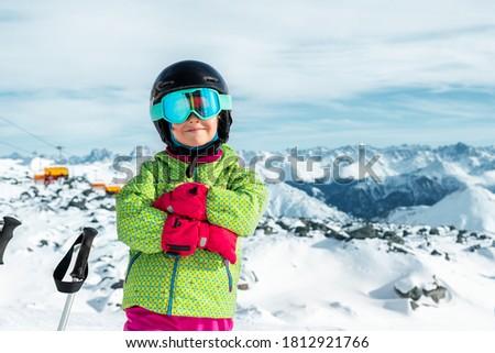 Active confident preschooler caucasian kid girl portrait with ski in helmet, goggles and bright suit enjoy winter extreme sport activities. Little child skiing on luxury alpine resort in mountains