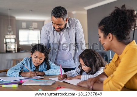Indian parents helping children with their homework at home. Middle eastern father and african mother helping daughters studying at home. Little girls completing their exercises with the help of dad. Royalty-Free Stock Photo #1812937849