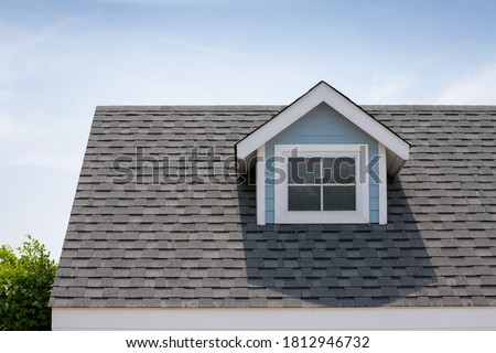 Roof shingles with garret house on top of the house among a lot of trees. dark asphalt tiles on the roof background Royalty-Free Stock Photo #1812946732