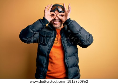 Young handsome skier man skiing wearing snow sportswear using ski goggles doing ok gesture like binoculars sticking tongue out, eyes looking through fingers. Crazy expression. #1812950962
