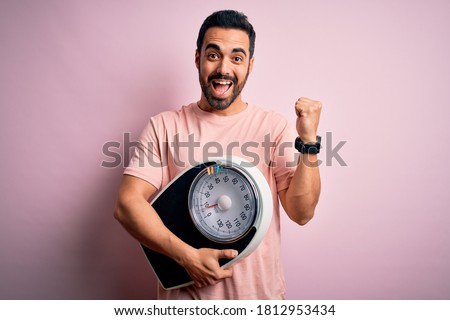 Young handsome slim sportsman with beard holding scale over isolated pink background screaming proud and celebrating victory and success very excited, cheering emotion Royalty-Free Stock Photo #1812953434