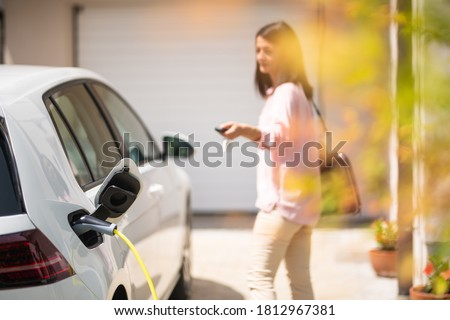 Close up of a electric car charger with female silhouette in the background, locking a car Royalty-Free Stock Photo #1812967381