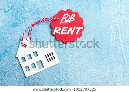 House for rent label on christmas holidays. Wooden house symbol with rent tag on blue background. Real estate, rental housing, rent for winter holidays concept. Top view Royalty-Free Stock Photo #1812987325