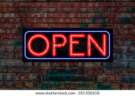 Open sign in Neon light on a gunge brick wall. Open for business