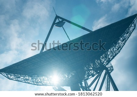 Huge satellite antenna dish for communication and signal reception out of the planet Earth. Observatory searching for radio signal in space at sunset. Royalty-Free Stock Photo #1813062520