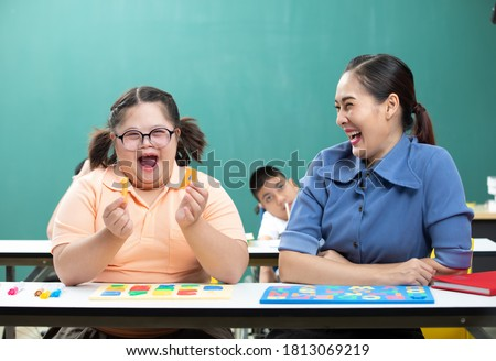 portrait asian disabled child or down syndrome child showing alphabet toy puzzle and woman teacher helping in classroom Royalty-Free Stock Photo #1813069219