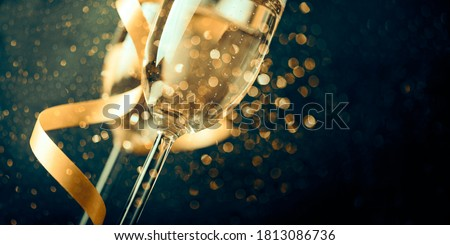 Two champagne glasses with golden ribbon and gold glitter splash bokeh on dark background. Luxury restaurant dinner celebration. Classy christmas and new year holiday panoramic design banner. #1813086736