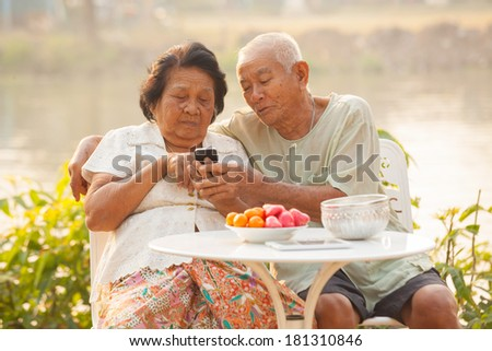 Happy asian senior couple using the mobile phone on outdoor background #181310846