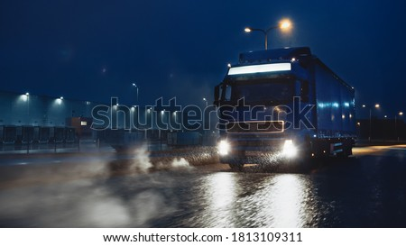 Blue Long Haul Semi-Truck with Cargo Trailer Full of Goods Travels At Night on the Freeway Road, Driving Across Continent Through Rain, Fog, Snow. Industrial Warehouses Area. #1813109311