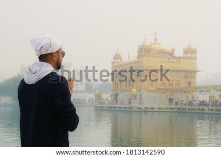 Wide angle picture of Indian man wearing white turban praying in front of the holy lake at Sri Harmandir Sahib, known as Golden Temple, site of Sikhism, located in Amritsar, Punjab, India.