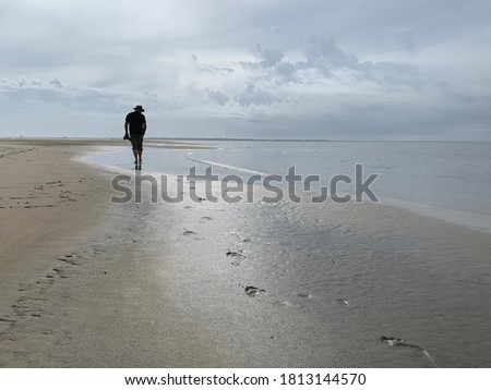 Man walking along a deserted shoreline under a moody sky, while leaving footprints in the sand Royalty-Free Stock Photo #1813144570