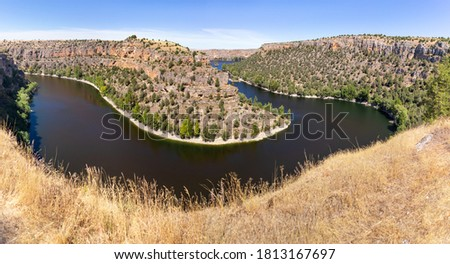 Famous meander of Duratón river among cliffs, near romanesque church Ermita de San Frutos. Home of the griffon vultures. Panoramic picture. Hoces del Duratón (Duraton gorges), Segovia, Madrid, Spain