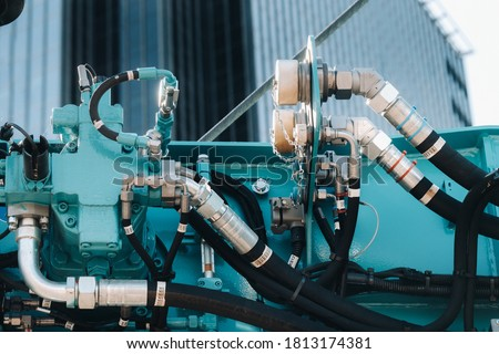 Hydrostatic crane engine.The control system of the crane engine.Lifting hydraulic Department on the truck crane.The hydraulic system of the engine.hydraulic hoses on the crane.autoparts Royalty-Free Stock Photo #1813174381
