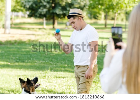 Young latino man playing and training with his border collie dog while his girlfriend takes a picture of him with her cell phone