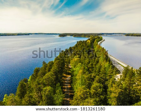 Network of waters and islands,which are connected by narrow straits creating unique lakeland labyrinth around the Lake Saimaa. Aerial picture of the road between trees in Punkaharju Savonlinna Finland