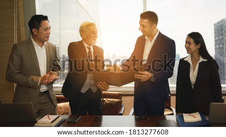 caucasian and asian business people having business agreement in signing ceremony in boardroom