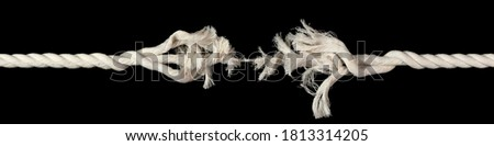 Cotton rope, frayed and ready to break apart with rope held together by last strand ready to snap. Concept of danger or stressful situation like divorce separation, deadlines, failure, or tension. Royalty-Free Stock Photo #1813314205