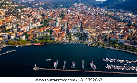 Italy, Como, 09/10/2020: Aerial view of the port of Lake Como. city center. A local ferry arrives in the city. This ferry transports people between different cities by the lake. Boat passing ahead #1813352062
