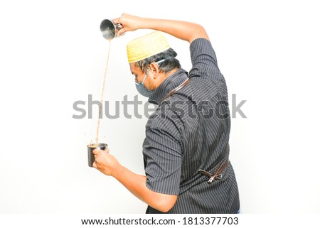 """A picture of men preparing famous Malaysia drink call """"teh tarik"""". Sweet milk tea been pull for mix well and create foam that is famous in Malaysia and South Asia region."""