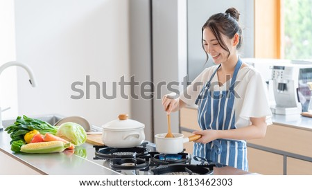 attractive asian woman cooking at kitchen Royalty-Free Stock Photo #1813462303
