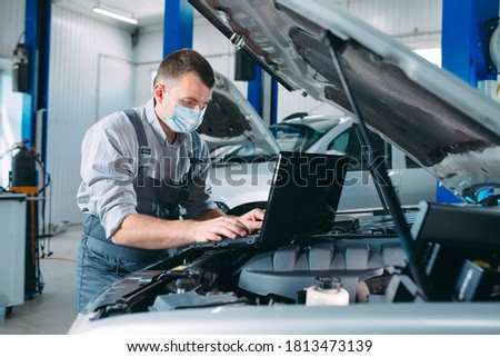 car mechanic using a computer laptop to diagnosing and checking up on car engines parts for fixing and repair Royalty-Free Stock Photo #1813473139