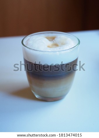 picture of a cup of coffe with milk into a white table