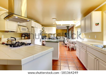 Ivory wall kitchen room with white storage combination and brown tile floor. View of the dining area #181364249