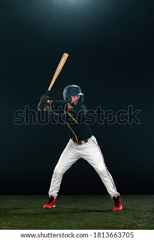 Baseball player with bat on dark background. Ballplayer portrait. Royalty-Free Stock Photo #1813663705
