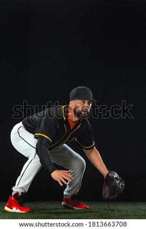 Baseball player on dark background. Ballplayer portrait. Royalty-Free Stock Photo #1813663708