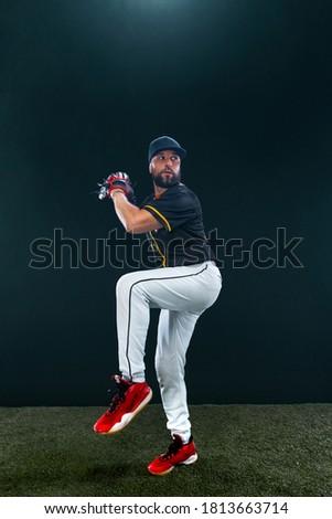 Baseball player on dark background. Ballplayer portrait. Royalty-Free Stock Photo #1813663714