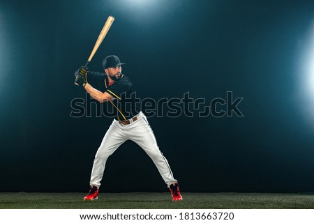 Baseball player with bat on dark background. Ballplayer portrait. Royalty-Free Stock Photo #1813663720