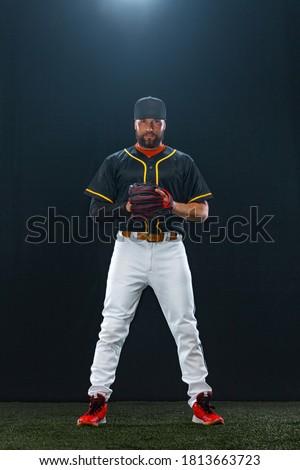 Baseball player on dark background. Ballplayer portrait. Royalty-Free Stock Photo #1813663723