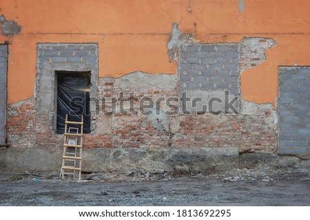 Brick wall of demolished building at construction site, with ladders and opening covered in plastic Royalty-Free Stock Photo #1813692295