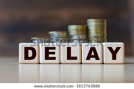 DELAY word on diced on a beautiful dark background with coins. Business concept Royalty-Free Stock Photo #1813763888
