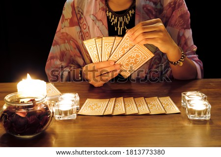 Tarot reading or fortune teller holding and picking tarot cards in her hands with burning candles and tarot cards spreading on a wooden table.Divination or forecasting concept. Royalty-Free Stock Photo #1813773380