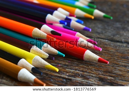 A close up image of sharpened wooden pencil crayons on a dark brown table top.