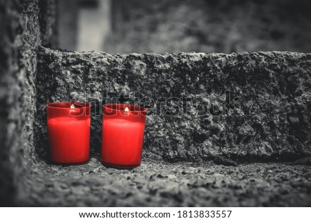 Two red candles on a grave. Lanterns on a tombstone at All Saints' Day in a cemetery. Shallow depth of field. Religion, funeral, mourning concept. Royalty-Free Stock Photo #1813833557