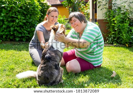 mentally disabled woman with a second woman and a companion dog, concept learning by animal assisted living Royalty-Free Stock Photo #1813872089