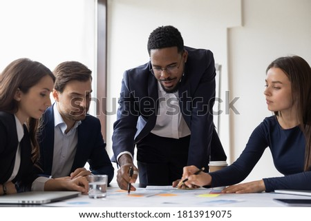 Confident African American businessman hold lead meeting with diverse colleagues in office. Multiracial businesspeople brainstorm discuss company financial paperwork at briefing. Teamwork concept. Royalty-Free Stock Photo #1813919075