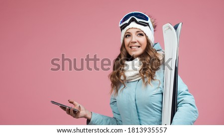 young woman with skis uses a smartphone to plan her ski runs. Winter holidays at a ski resort. woman with a hat and skis on a pink background #1813935557