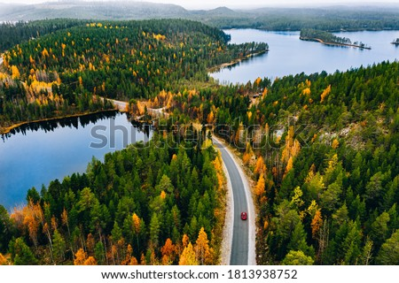 Aerial view of rural road with red car in yellow and orange autumn forest with blue lake in Finland.