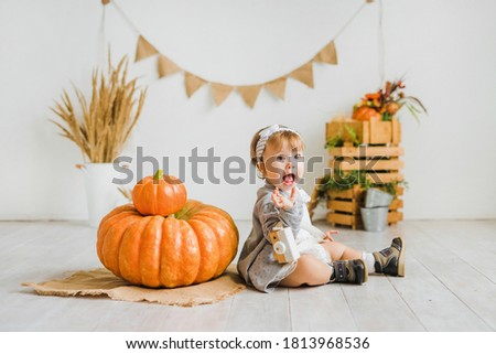 Little girl plays with a big pumpkin. Children's photo zone in autumn style.