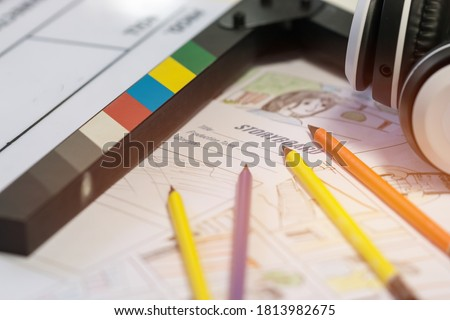 Storyboard Video for Pre-production on film movie concept: Color pencil drawing on sketch board cartoon template with headphone on slate, Behind process design creative scene in studio
