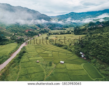 Beautiful aerial view of rice paddy field in Sapan village a small village nestled in a forested northern valley of pure air and pristine rivers in Nan province of Thailand. Royalty-Free Stock Photo #1813983065