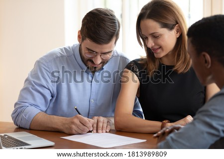 Happy young couple sit at desk meet with realtor put signature on contract buying first house together, excited husband and wife sign business agreement close deal with agent at office meeting